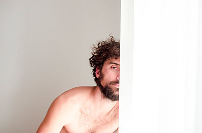 shirtless man with half covered face in a room with soft light  - p1656m2248585 by Javier Martinez Bravo
