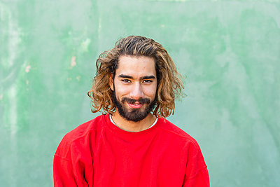 Portrait of bearded young man wearing red sweatshirt in front of green wall - p300m2159848 by VITTA GALLERY