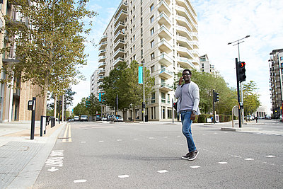 Professional talking on phone while crossing street in city - p300m2241582 von Pete Muller