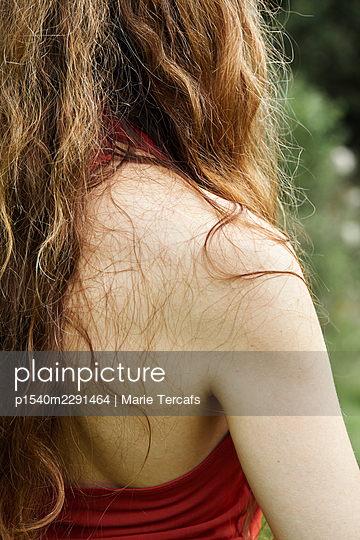 back of long haired redhead woman in nature - p1540m2291464 by Marie Tercafs