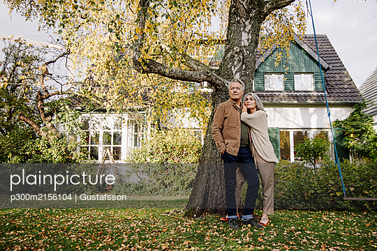 Senior couple in garden of their home in autumn - p300m2156104 by Gustafsson