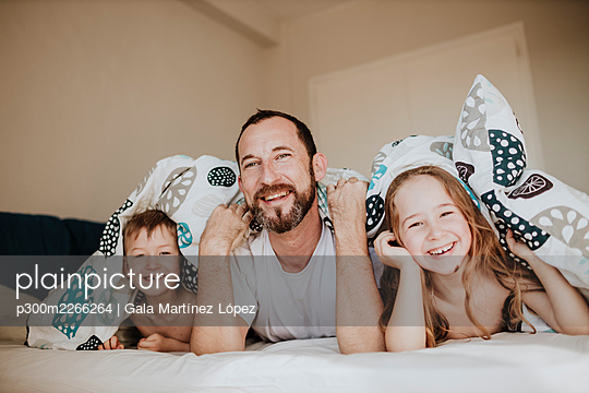 Smiling father with daughter and son lying on bed under blanket in bedroom at home - p300m2266264 by Gala Martínez López
