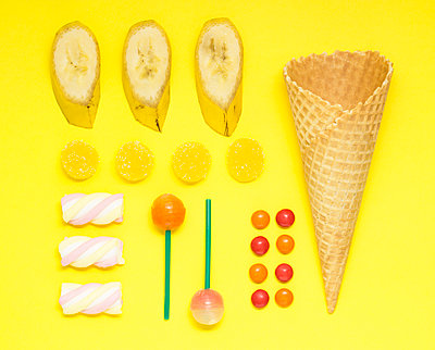 Overhead view of waffle cone with bananas and colorful candies on yellow background - p1166m1576143 by Cavan Images