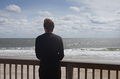 Back view of a young man looking out over the ocean on a sunny day - p1694m2291681 by Oksana Wagner