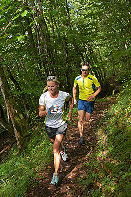 Joggers running in forest - p429m2074450 by Ross Woodhall