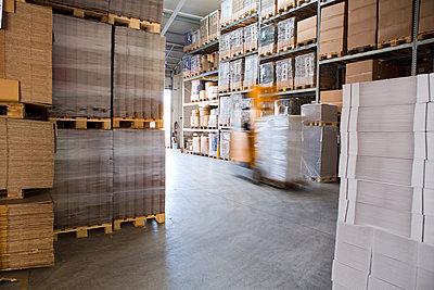 Blurred forklift truck in storage warehouse - p429m942790f by Judith Haeusler