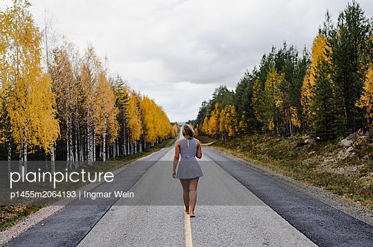 Woman is walking down a road in Lappland during autumn - p1455m2064193 von Ingmar Wein