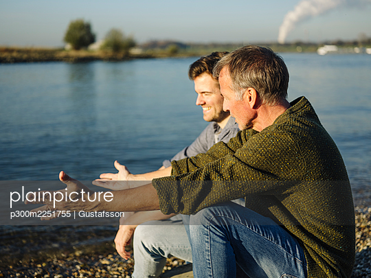 Father gesturing while talking with son by lake on sunny day - p300m2251755 by Gustafsson