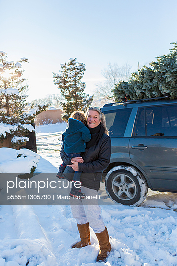 Caucasian mother holding son in snow - p555m1305790 by Marc Romanelli