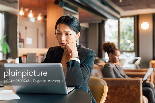 Italy, Businesswoman using laptop at table in creative studio - p924m2300743 by Eugenio Marongiu