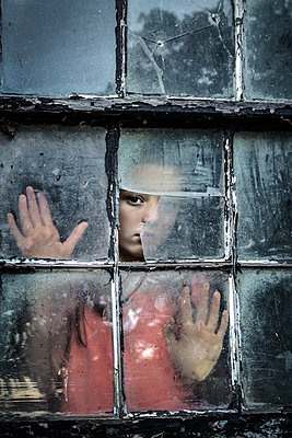 Teenage Girl looking out broken old window - p1019m1487229 by Stephen Carroll