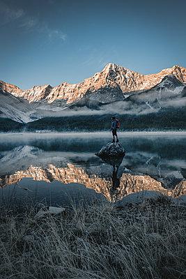 Junger Mann steht auf einem Stein im Wasser mit Bergpanorama im Hintergrund - p1455m1574497 von Ingmar Wein