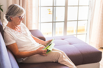 Senior woman sitting on the couch using tablet - p300m1449485 by Simona Pilolla
