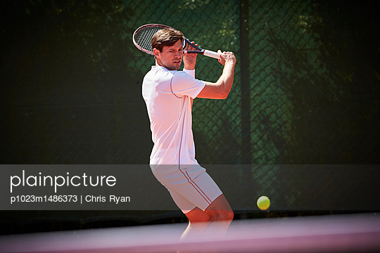 Young male tennis player playing tennis, swinging at tennis ball on sunny tennis court