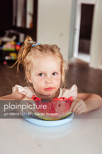 Little girl eating a watermelon - p1166m2157137 by Cavan Images