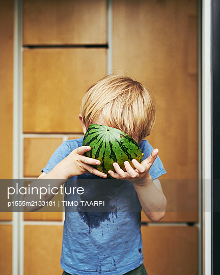 Boy eating melone - p1555m2133181 by TIMO TAARPI