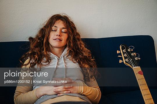 Junge Frau mit roten Haaren entspannt sich - p586m1200152 von Kniel Synnatzschke