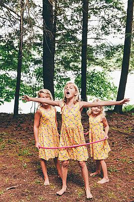 Drei Mädchen spielen Mit Hula-Hoop-Reifen - p1086m2149981 von Carrie Marie Burr