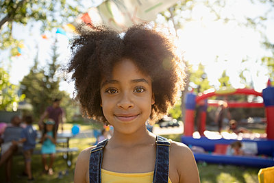 Portrait smiling, cute girl at summer neighborhood block party in park - p1192m2017095 by Hero Images