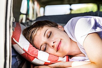 Smiling woman sleeping in a van - p300m2069776 by Jo Kirchherr