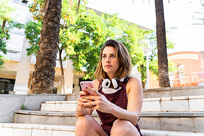 Young woman using smartphone, heaphones around her neck - p300m2131674 von VITTA GALLERY