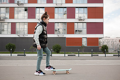 Girl with skateboard standing on road against building in city - p300m2198184 by Ekaterina Yakunina
