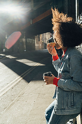 Afro young woman eating donut while standing on street during sunny day - p300m2213906 by Boy photography