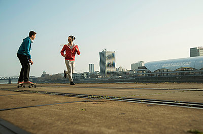 Young man and teenager jogging and skateboarding - p300m982284f by Uwe Umstätter