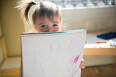 Caucasian baby girl showing drawing on sketchpad - p555m1481913 by JGI