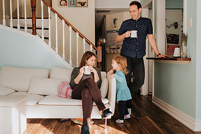 Mid adult couple having mug of coffee in living room with toddler daughter - p924m2077775 by Sara Monika