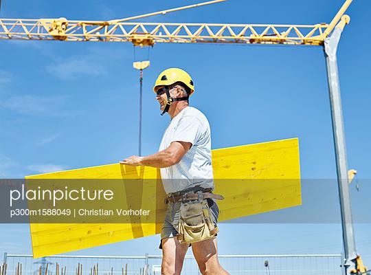 plainpicture - plainpicture p300m1588049 - Construction worker carryin... - plainpicture/Westend61/Christian Vorhofer