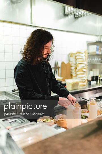Male chef preparing food in kitchen at restaurant - p426m2279873 by Maskot