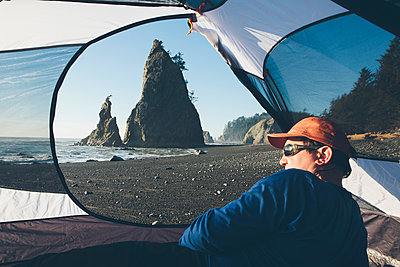 Man sitting in camping tent, Rialto Beach in distance, Olympic National Park, Washington, USA. - p1100m1425087 by Mint Images