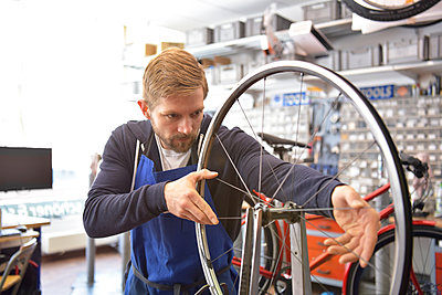 Bicycle mechanic in his repair shop, portrait - p300m1587471 by lyzs