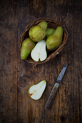 Whole and sliced organic pears 'Conference' with pocket knife on dark wood - p300m2070319 by Larissa Veronesi
