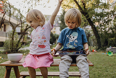 Brother and little sister in the garden with digital tablet - p300m2080467 by Johanna Lohr