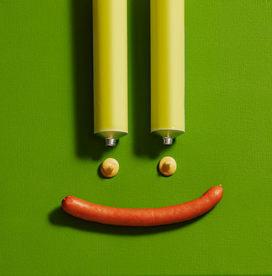 Directly above shot of anthropomorphic smiley face made with mustard sauce tubes and sausages on green canvas - p300m2144225 by Kai Schwabe