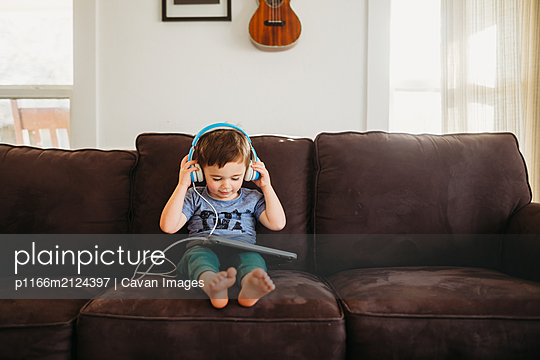 Young boy putting on headphones and using tablet at home - p1166m2124397 by Cavan Images