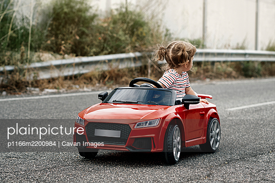 A girl riding a toy car - p1166m2200984 by Cavan Images