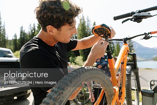 Man adjusting seat of mountain bike - p1192m2129194 by Hero Images
