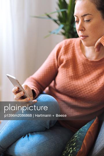 Frau schaut auf ihr Smartphone - p1396m2086868 von Hartmann + Beese