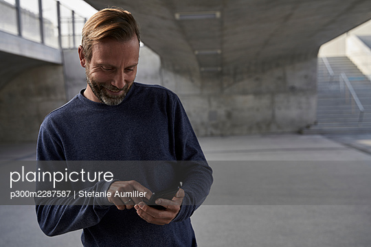 Smiling male professional text messaging through smart phone while standing under bridge - p300m2287587 by Stefanie Aumiller