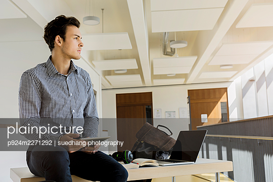Germany, Bavaria, Munich, Young man sitting on desk with digital tablet - p924m2271292 by suedhang photography