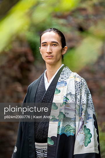 UK, Portrait of young man wearing kimono in park - p924m2300776 by Kaori Ando