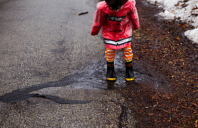 Boy playing in puddle on street - p1166m1474021 by Cavan Images