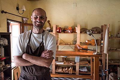 Portrait of smiling luthier in his workshop - p300m1157334 by Andrés Benitez