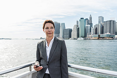 USA, Brooklyn, portrait of pensive businesswoman standing on boat - p300m1205280 by Uwe Umstätter