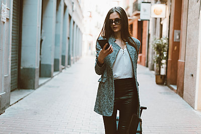 Young businesswoman in the city checking cell phone - p300m1568352 by Oriol Castelló Arroyo