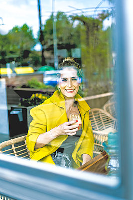 Portrait of smiling woman behind windowpane in a cafe - p300m2103129 by Eloisa Ramos