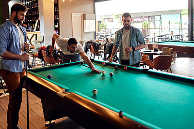 Friends playing billiards together - p300m2104556 by Zeljko Dangubic